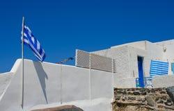 Vecchia via bianca in Santorini con la bandierina della Grecia Fotografia Stock