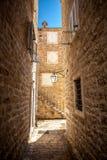 Vecchia via stretta con le alte costruzioni al giorno soleggiato Fotografie Stock Libere da Diritti