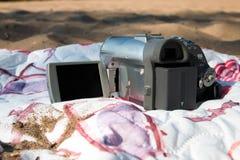 Vecchia videocamera sulla spiaggia, su un copriletto colorato, sulla sabbia immagine stock