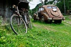 Vecchie automobile e bicicletta d'annata nel villaggio Immagine Stock