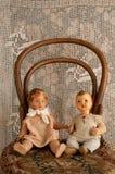 Vecchie bambole della ragazza e del ragazzo su una vecchia presidenza con un merletto Fotografia Stock