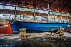 Vecchie barche arrugginite in capannone nella fabbrica di riparazione Immagine Stock