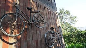 Vecchie biciclette classiche che appendono sulla parete di legno fotografia stock