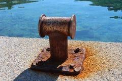 Vecchie bitte arrugginite di attracco del ferro sul pilastro locale con il mare nel fondo Fotografie Stock