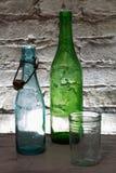 Vecchie bottiglie e un vetro Fotografia Stock Libera da Diritti
