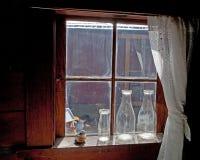 Vecchie bottiglie nella finestra della fattoria Fotografia Stock