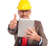 Vecchie buone notizie della lettura dell'ingegnere di costruzione sul suo cuscinetto della compressa Fotografia Stock