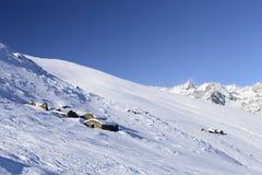 Vecchie capanne del pascolo nel fondo scenico di inverno Immagini Stock