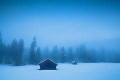 Vecchie capanne e foresta di conifere in nebbia di inverno Fotografia Stock Libera da Diritti