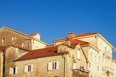 Vecchie case con i tetti rossi sotto cielo blu Città antica di Perast, Montenegro Immagini Stock