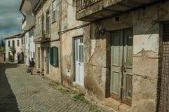 Vecchie case con la parete incrinata del gesso in un vicolo con il pedone fotografia stock