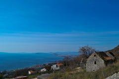 Vecchie case del villaggio alla vista del briciolo della scogliera a cielo blu ed al mare Fotografie Stock