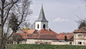 Vecchie case del villaggio con la facciata incrinata e la torre di chiesa bassa Fotografia Stock