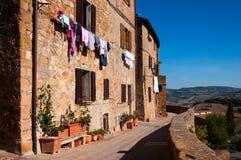 Vecchie case di pietra con abbigliamento colorato Pienza, Italia Immagine Stock