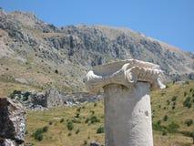 Vecchie colonna e montagne ioniche come fondo Immagini Stock