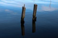 Vecchie colonne di legno del molo che sporgono dal mare Fotografie Stock