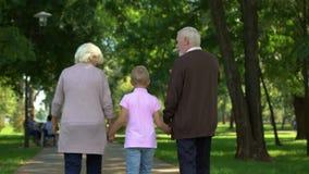 Vecchie coppie che camminano con il ragazzo in parco, tenentesi per mano, supporto sociale di adozione stock footage