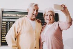 Vecchie coppie che prendono foto in aeroporto nella sala di attesa fotografia stock