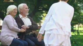 Vecchie coppie che si siedono sul banco e che guardano felicemente loro divertiresi dei nipoti video d archivio
