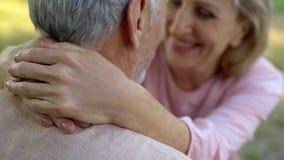 Vecchie coppie felici che abbracciano nel parco, pensionamento comodo, vecchiaia sicura, amore fotografie stock