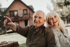 Vecchie coppie felici che guardano da parte con l'interesse Immagini Stock Libere da Diritti