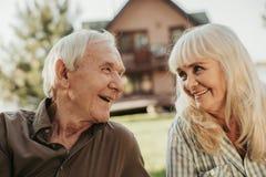 Vecchie coppie felici che si siedono al prato inglese che fronteggia casa Fotografia Stock