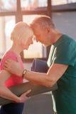 Vecchie coppie felici con le stuoie di yoga che toccano le fronti Immagini Stock Libere da Diritti