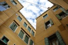 Vecchie costruzioni con le pareti gialle e gli otturatori di legno verdi Immagini Stock Libere da Diritti