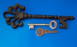 Vecchie e nuove chiavi sui precedenti blu fotografia stock libera da diritti