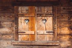 Vecchie finestre di legno di una casa di legno con due ritagli dei cuori immagini stock