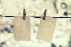 Vecchie foto in bianco che appendono sulla corda da bucato Fotografie Stock