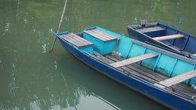 Vecchie imbarcazioni a remi di pesca al pilastro sull'acqua stock footage