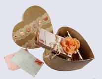 Vecchie lettere di amore d'annata in una mano della scatola del biglietto di S. Valentino decorata con i bottoni ed il pizzo fotografie stock