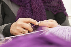 Vecchie mani dei womans che lavorano a maglia una sciarpa Fotografia Stock