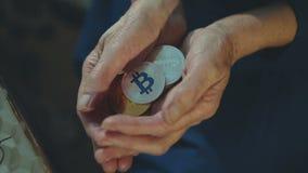 Vecchie mani femminili corrugate che tengono molti bitcoins dorati e d'argento stock footage