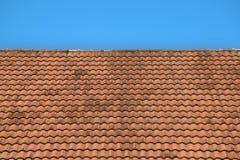 Vecchie mattonelle di tetto rosse struttura e fondo del cielo blu Immagini Stock