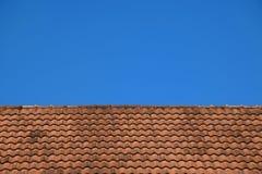 Vecchie mattonelle di tetto rosse struttura e fondo del cielo blu Immagini Stock Libere da Diritti