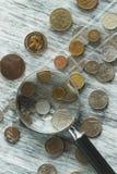 Vecchie monete e lente d'ingrandimento differenti, fondo molle del fuoco Fotografia Stock Libera da Diritti
