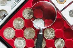 Vecchie monete e lente d'ingrandimento differenti, fondo molle del fuoco Fotografie Stock Libere da Diritti