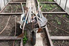 Vecchie pale sporche del giardino, rastrelli, zappe nel carretto, nella serra fotografia stock libera da diritti