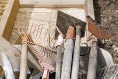 Vecchie pale sporche del giardino, rastrelli, zappe in un carrello immagine stock libera da diritti