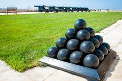 Vecchie palle di cannone impilate in piramide, davanti ai cannoni, sul castello di La Valletta, Malta Fotografie Stock Libere da Diritti