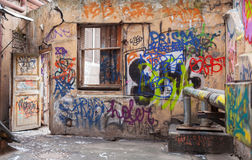 Vecchie pareti del cortile dipinte con i graffiti caotici variopinti Fotografia Stock