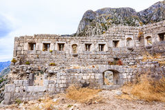 Vecchie pareti di pietra della fortificazione medievale, rovine della città contro la montagna in Cattaro, Montenegro di Lovcen Immagine Stock
