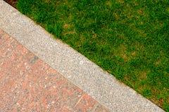 Vecchie pavimentazione ed erba del granito nella struttura decorativa del giardino, linea che divide natura e civilizzazione, con Immagini Stock Libere da Diritti