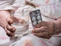 Vecchie pillole tristi della tenuta della donna fotografia stock libera da diritti