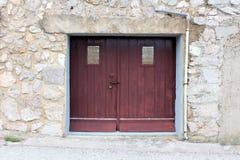 Vecchie porte di legno del garage fatte dei bordi di legno e della protezione di pioggia di gomma chiusi a chiave con il fermo ed fotografie stock