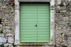 Vecchie porte verdi d'annata in un recinto della parete di pietra Immagine Stock Libera da Diritti