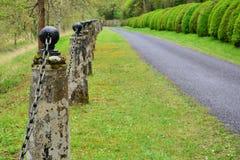Vecchie poste di pietra con il recinto del collegamento a catena del ferro Fotografia Stock