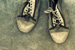 Vecchie retro scarpe di palestra sporche sul lerciume un fondo Vecchi pattini di sport Immagine Stock